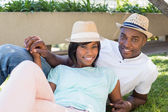 Happy couple lying in garden together cuddling — Stock Photo