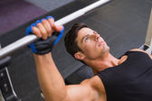 Determined muscular man lifting barbell in gym — Stok fotoğraf