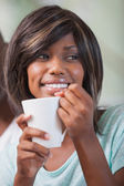 Happy woman sitting on couch having coffee — Stock Photo