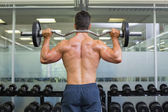 Rear view of a muscular man lifting barbell — Stock Photo