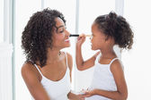 Cute daughter putting makeup on her mothers face — Photo