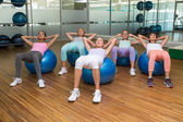 Fitness class doing sit ups on exercise balls in studio — Stok fotoğraf
