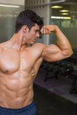 Muscular man flexing muscles in gym — ストック写真