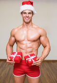 Shirtless macho man in santa hat holding gifts — Stockfoto