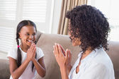 Pretty mother playing clapping game with daughter — Stock Photo