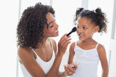 Pretty mother teaching her daughter about makeup  — Stockfoto