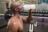 Sporty young man drinking protein in gym — Stock Photo