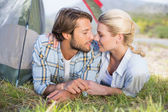 Couple lying in their tent about to kiss — Stockfoto