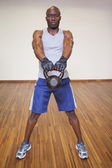 Muscular man exercising with kettle bell in gym — Stock Photo
