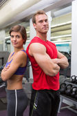 Fit attractive couple smiling at camera with arms crossed — Stock Photo