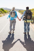 Couple on the road holding hands — Stock Photo