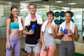 Fit man and women smiling at camera in studio — 图库照片