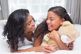Pretty woman lying on bed with her daughter — Stock Photo