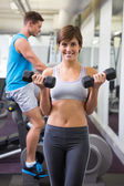 Fit brunette lifting weights smiling at camera — Stock Photo