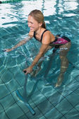 Blonde using underwater exercise bike — Stock Photo