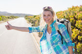 Blonde hitch hiking on rural road — Stock Photo