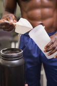 Body builder holding a scoop of protein mix — Stock Photo