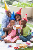 Family celebrating a birthday together in the garden — Stock Photo