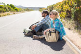Couple sitting on road waiting for lift — Stock Photo