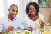 Couple enjoying a healthy meal together smiling at camera — Stock Photo
