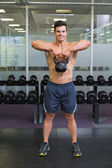 Muscular man lifting kettle bell in gym — ストック写真