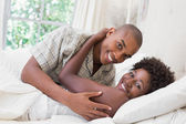 Intimate couple cuddling lying on their bed — Stock Photo