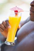 Shirtless man drinking orange cocktail — Stock Photo