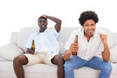 Nervous sports fans sitting on the couch with beers — Photo