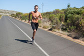 Athletic man jogging on open road with monitor around chest — Photo