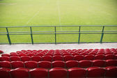 Red bleachers looking down on football pitch — Stock Photo