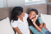 Happy mother and daughter on the phone together on sofa — Stock Photo