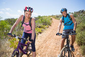 Couple cycling down mountain trail — Foto de Stock