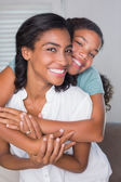 Happy mother and daughter hugging on the couch — Stock Photo