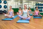 Smiling yoga class in lotus pose in fitness studio — Stock Photo