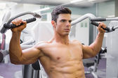 Muscular man working on fitness machine at the gym — Stock Photo