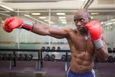 Boxer attacking with his right in health club — Stock Photo