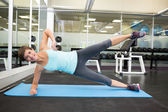 Fit smiling brunette doing pilates on exercise mat — 图库照片