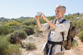 Handsome hiker taking a photo in the countryside — Stock Photo