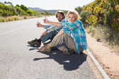 Couple sitting on road hitching lift — Stockfoto