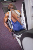 Male weightlifter doing leg presses in gym — Stockfoto