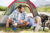 Happy couple cooking on camping stove — Stock Photo