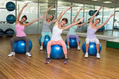 Fitness class sitting on exercise balls in studio — Stockfoto
