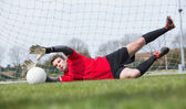 Goalkeeper in red saving a goal during a game — Foto Stock