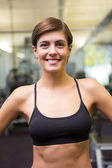 Fit brunette in black sports bra smiling at camera — Stock Photo