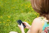 Woman text messaging in field — Stock Photo