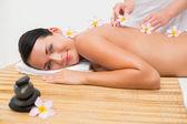 Beautiful brunette enjoying a flower back massage  — Stock Photo
