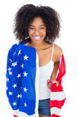 Pretty girl wrapped in american flag smiling at camera — Stock fotografie