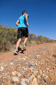 Athletic man jogging up country trail — Stock Photo