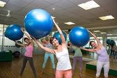 Fitness class holding up exercise balls in studio — Stockfoto