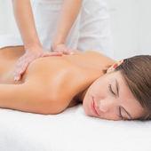 Attraktive frau empfangen rückenmassage im spa-center — Stockfoto